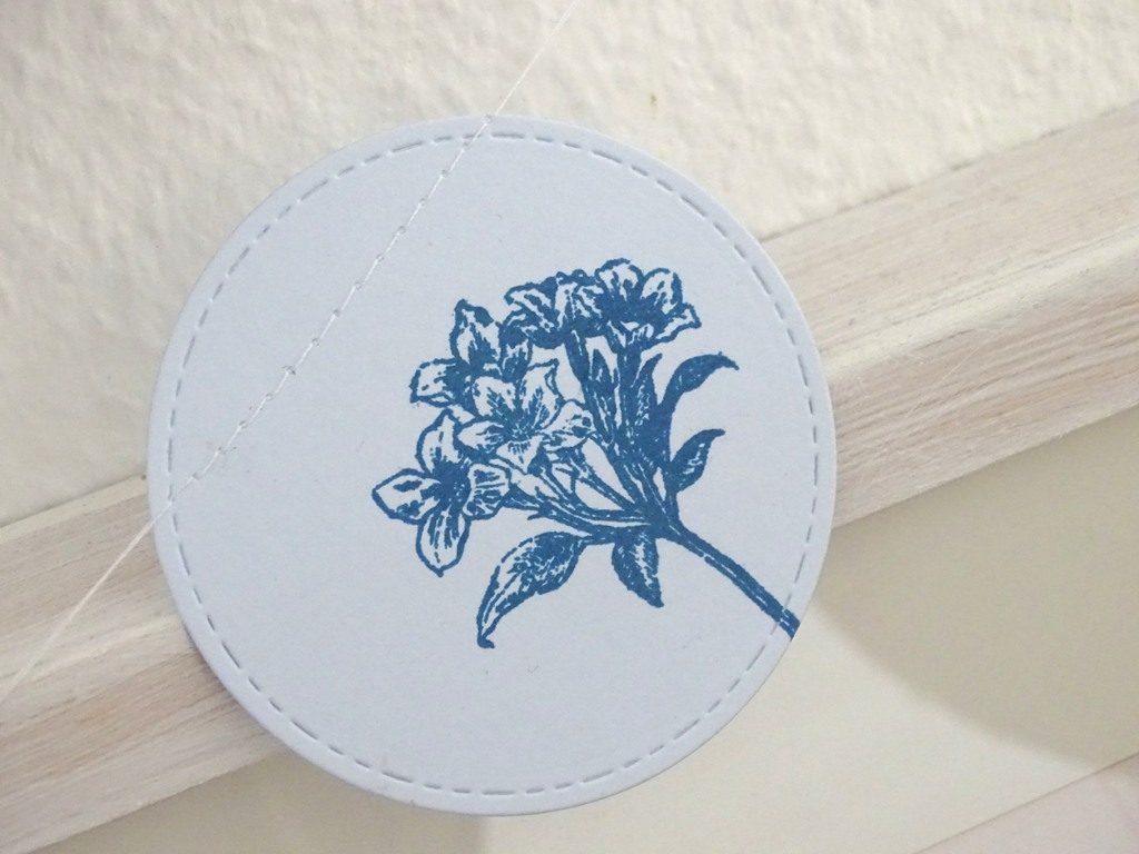 Bastle Dir eine Ostergirlande aus buntem Papier und mit frühlingshaften Blumenstempeln