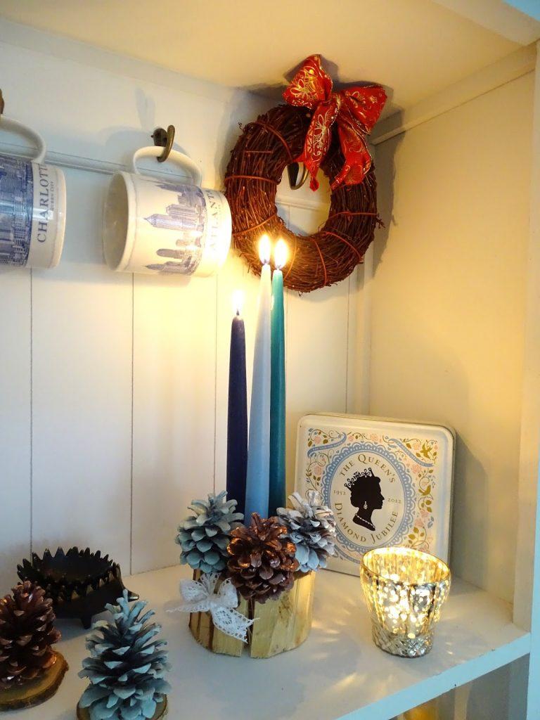 Weihnachtsdeko mit Kerzen, Bockerln und Zapfen, Astscheiben
