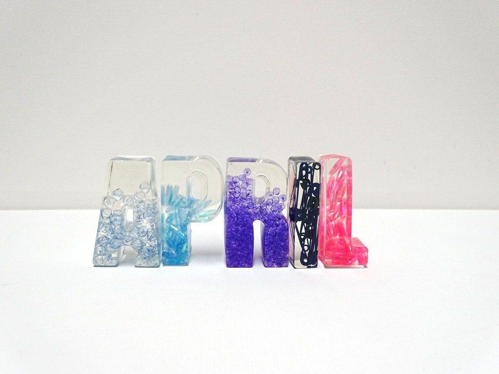 April: Buchstaben aus Epoxidharz mit eingegossenen Glasperlen
