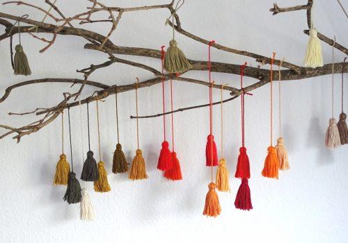 Naturdeko: Ast mit Quasten aus Garn