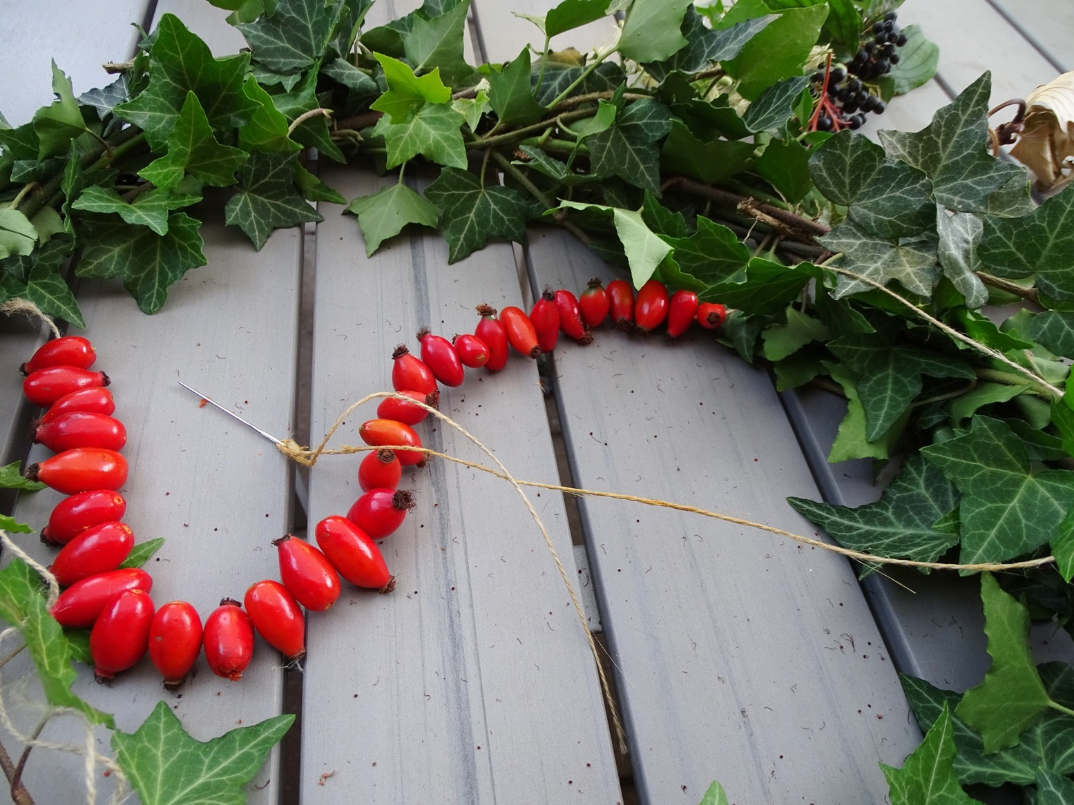 Hagebuttenketten fädeln für Herbstdeko im Garten