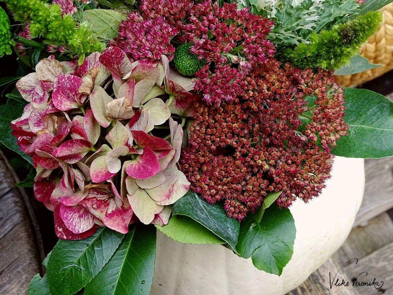 Ein Kürbis kann auch als Vase fungieren! Dekoriere ihn mit Blumen, die Du in ein Marmeladeglas stellst.