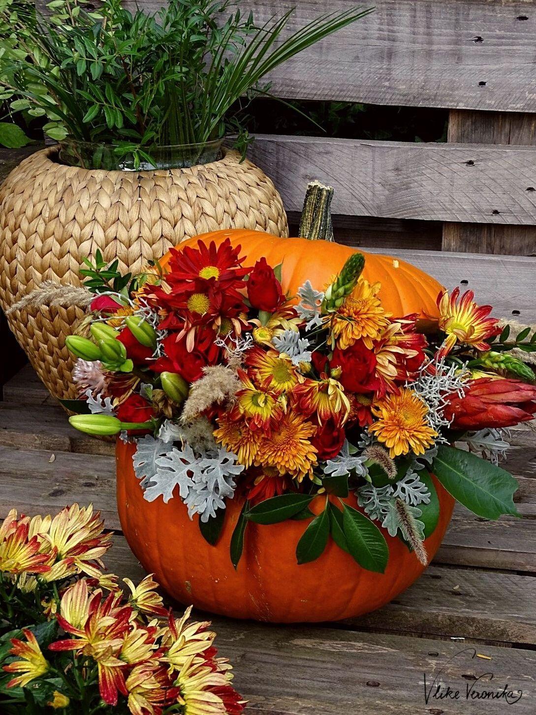 Orange, Rot, Grün und Blaugrau - die Farben für den Kürbis mit Blumendeko im Herbst.