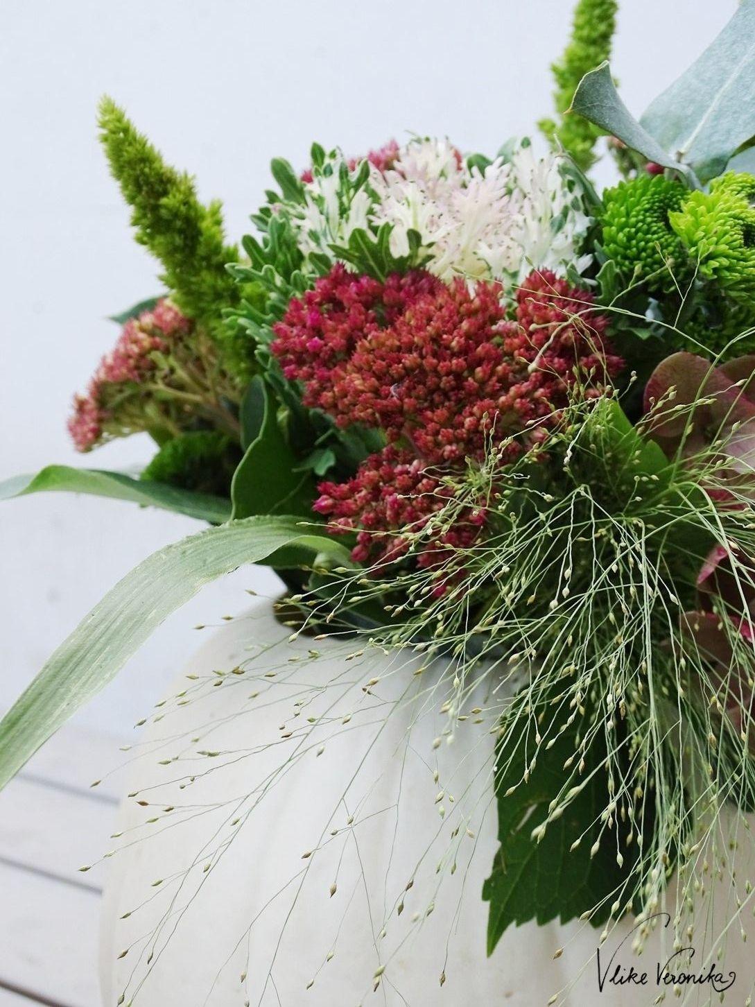 Zarte Gräser und wuchtige Herbstblumen - so schön kann Blumendeko im Kürbis sein.
