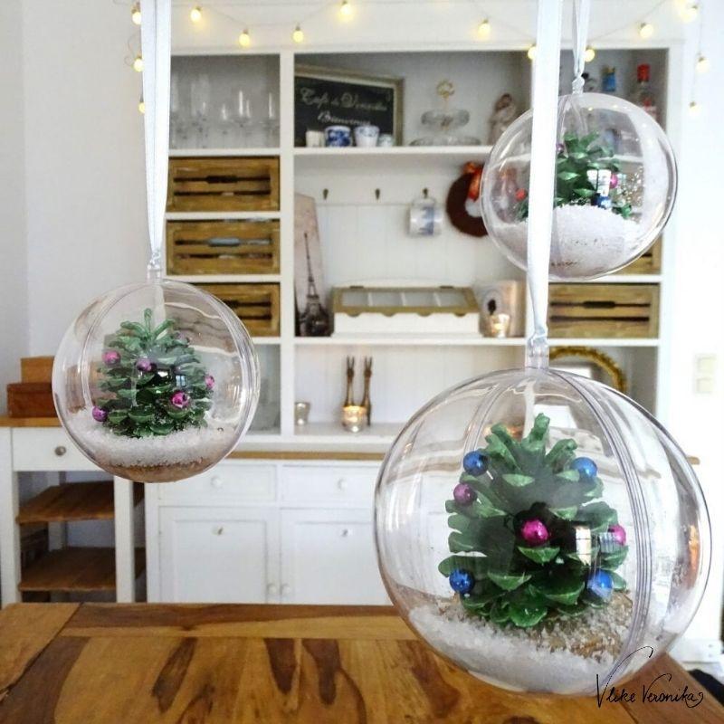 Bastelideen für den Advent mit Kindern: Schneekugeln aus Kiefernzapfen findest Du bei VlikeVeronika aus Wien.